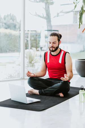Mexican guy meditating with closed eyes listening to yoga instructor online at home in Latin America Stock fotó