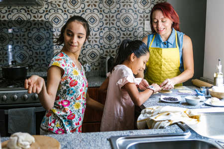 Mexican teenage female with cerebral palsy making cookies with her sister and mother in the kitchen, in disability concept in Latin America