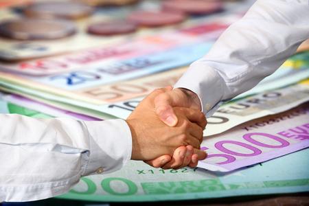euro banknotes:  Handshake and Euro Banknotes Background Stock Photo