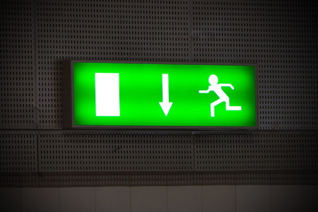 Emergency exit sign above a black doorway