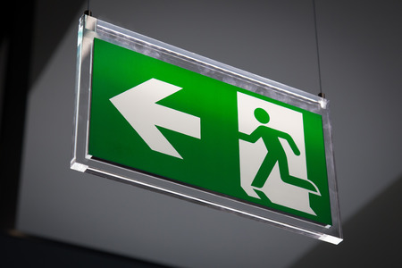 Emergency exit sign above a black doorway photo
