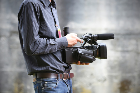 Video camera man with camera on gray background photo