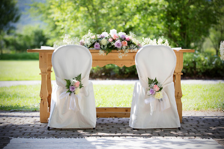 wedding decoration: Wedding Chairs Covers with Fresh Roses in a Wedding Day