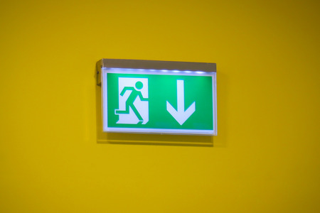 Emergency exit sign with a yellow background photo