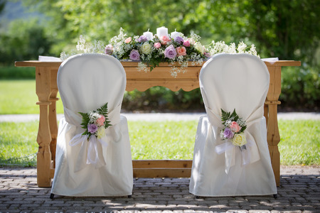 Wedding Chairs Covers with Fresh Roses in a Wedding Day