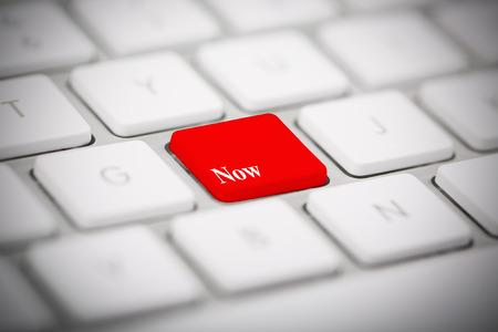 The word NOW written on metallic keyboard photo
