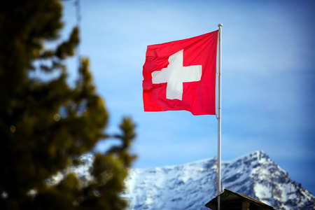 swiss culture: Switzerland flag Over Swiss Mountains in a Winter Day. Stock Photo