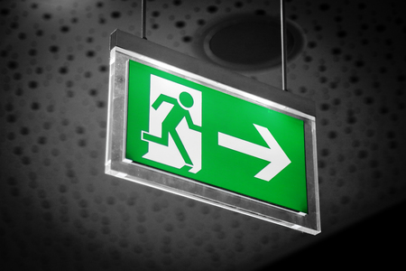 building safety: Emergency exit light sign on a gray background