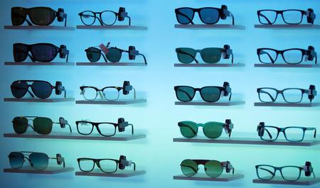 Optical store, many eyeglasses on blue background Stock Photo