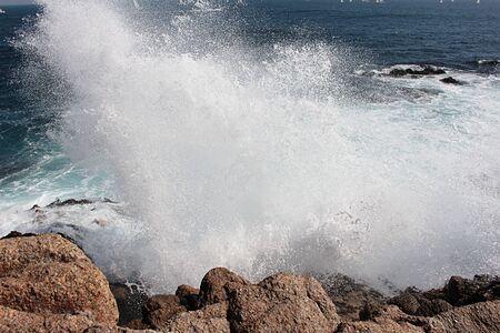 beautiful view of sea waves bursting in the rocks creating foam in Algarrobo beach in Chile