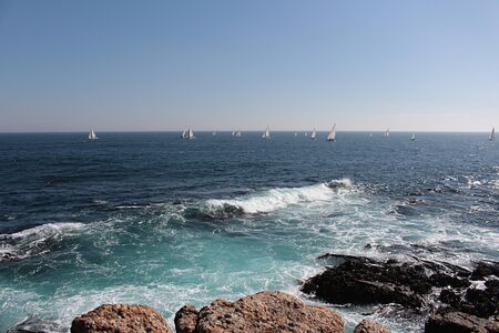 View of the sea with small sailboats near the horizon at noon in Algarrobo, central coast of Chile. Stok Fotoğraf
