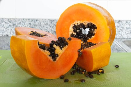 Delicious sweet orange papaya fruit cut on pieces on a green cutting board