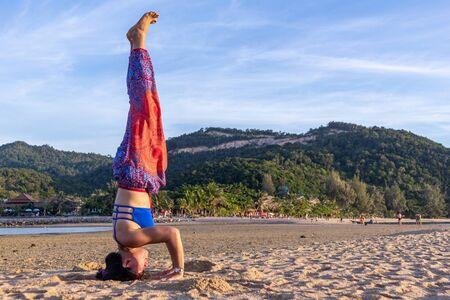 Asian Thai woman practicing yoga at evening in Mae Haad beach, Koh Phangan island, Thailand. Headstand tripod pose Фото со стока
