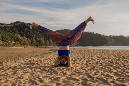 Asian Thai woman practicing yoga at evening in Mae Haad beach, Koh Phangan island, Thailand. Headstand supported pose with legs open.