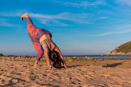 Asian Thai woman practicing yoga at evening in Mae Haad beach, Koh Phangan island, Thailand.
