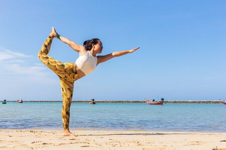 Asian Thai woman practicing yoga at evening in Haad Chaloklum beach, Koh Phangan island, Thailand. Lord of the dance pose. Imagens