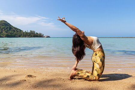 Asian Thai woman practicing yoga at evening in Haad Chaloklum beach, Koh Phangan island, Thailand. Camel pose.