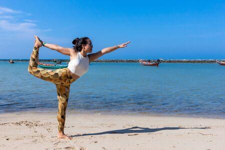 Asian Thai woman practicing yoga at evening in Haad Chaloklum beach, Koh Phangan island, Thailand. Lord of the dance pose. 免版税图像