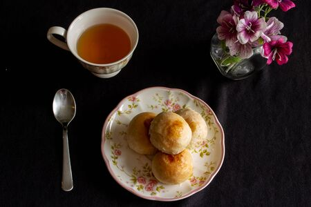 Traditional chinese cake on a plate with a cup of tea.