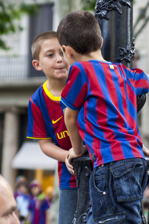 Barcelona, Spain - May 29, 2011. Kid celebrates the victory of  the Champions League of his team in catalunya square.