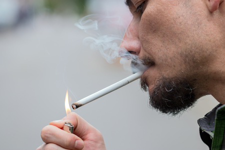 cigarette pack: Man pulls a cigarette from the pack and lights up