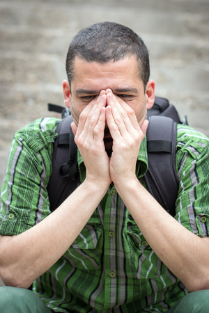 sitting on the ground: Despaired man covering his face with hands sitting on stairs