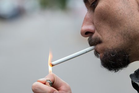 joven fumando: Man pulls a cigarette from the pack and lights up