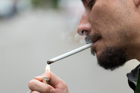 joven fumando: El hombre saca un cigarrillo del paquete y se ilumina Foto de archivo