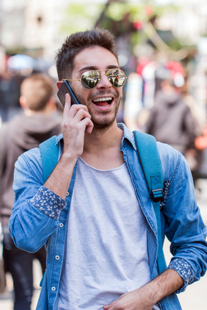 Man traveler with backpack talking on the phone in the background of the street. The concept of connection and communication in the journey, roaming. Stock Photo