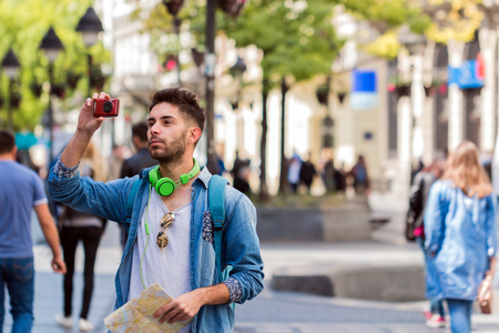 adult sex: Portrait of contemporary young man on solo trip in Europe, standing in street of old city looking at map tourist guide.