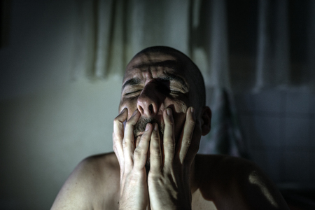 Men sit grief In the dark room because of disappointment in everything in life, both love and duty.Broken heart because of unrequited love, causing a man to shut himself. Stock Photo