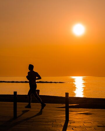 Silouhette of man jogging by the beach at sunrise Standard-Bild