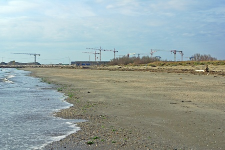 cranes on Mo. S.E. site, standin over the natural beach of Alberoni (Venice Lagoon), building a defence system for hig waters and flood in Venice Stock Photo
