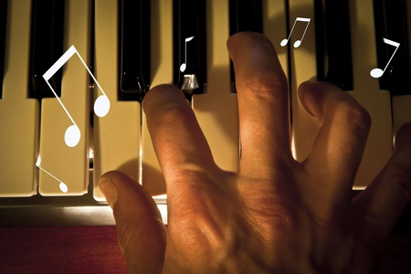 hand close up, playing a piano keyboard in low light
