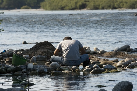 Marano Ticino, ITALY - MAY 30: A young man does gold panning at Ticino River on May 30, 2011 in Marano Ticino, Italy.
