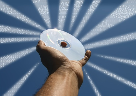 hand holds a cd with  blue sky  as background photo