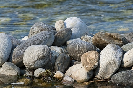 rock pile: pile of gray river rocks over an out of focus river background
