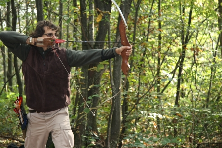 white caucasian Man takes aim with a recurve bow in the forest  photo