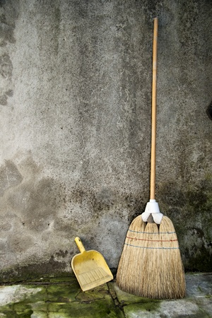 broom and dustpan over a grunge background