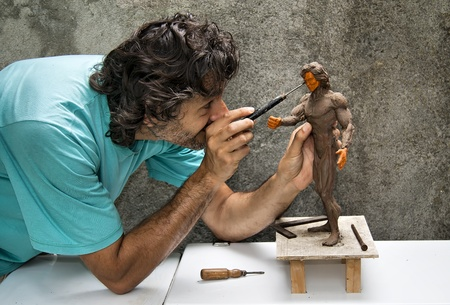 sculptor: sculptor working on a human figurine in clay  Stock Photo