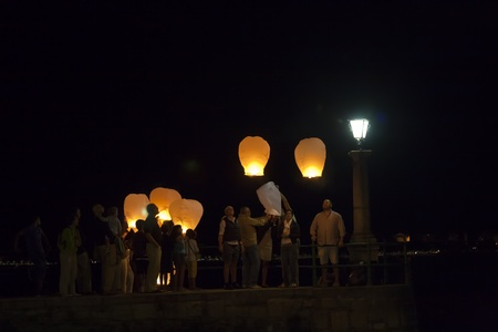 arona: Arona, ITALY - JULY 21:People light Chinese sky lanterns at the end of Taipei Philharmonic Youth & Childrens Choir performance on July 21, 2011 in  Piazza del Popolo, Arona, Italy