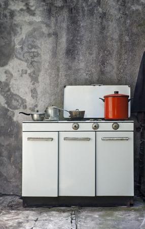 cocina antigua: estufa de gas viejo sobre un fondo de pared grunge  Foto de archivo