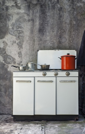 messy kitchen: old gas stove over a grunge wall background