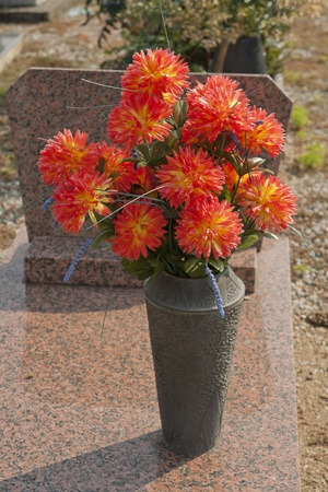 Headstone in a cemetery decorated with artificial flowers photo