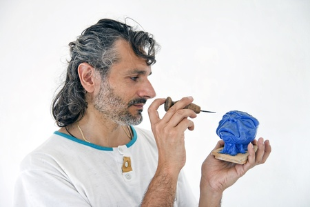 artist at work on a plasticine fantasy head miniature photo