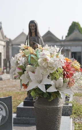 silk flowers vase on a gravestone in a cemetery Stock Photo