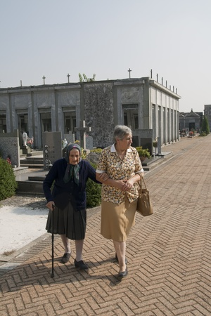 elderly people in a burial site on a sunny afternoon photo