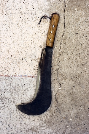 machete: vintage big sickle on a rustic wall