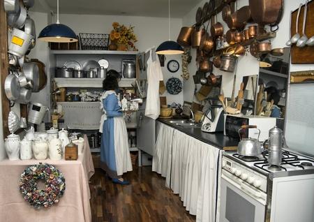 Senior maid working in an antique kitchen  Editorial