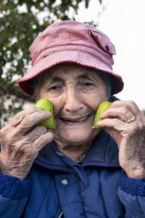 happy cheerful senior woman with two fig fruits